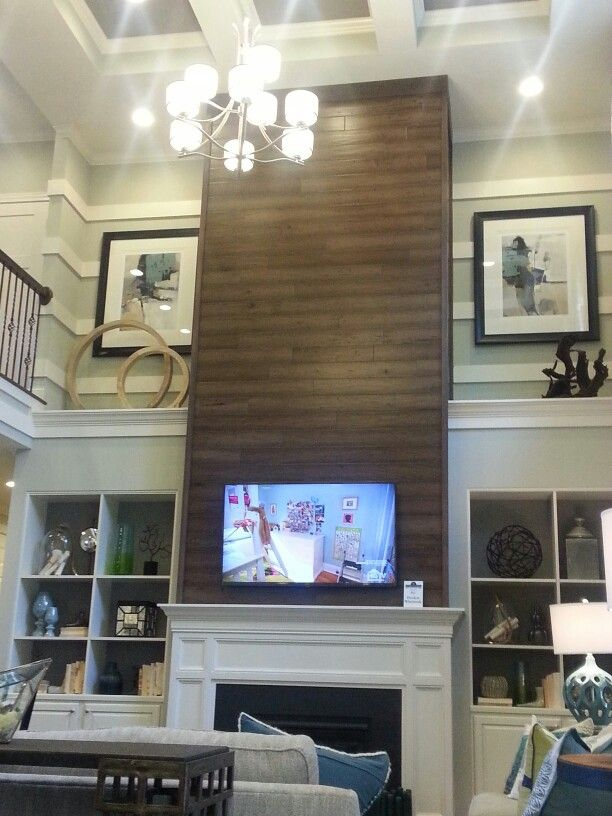 Two story Fireplace.  Perhaps stone on the bottom and white wood panels on top.                                                                                                                                                                                 More