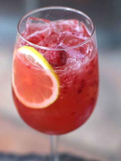 Sangria Recipes-Fruity Recipes for Sangria-A bright, sparkling sangria made with strawberries, gin, and Meyer lemon; then topped with sparkling wine. Visit redbookmag.com for more sangria recipes.