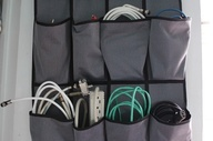 This solution is one of my favorites for garages, utility closets, and the like. Use a hanging shoe rack to store your unused wires, cords, and cables. Each pouch is the perfect size for one wound length of cord you'd find in a home or small office. You can also fill any extra slots with other small home improvement equipment, like containers of nails, or even lightweight tools.