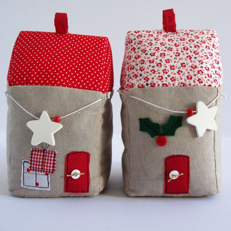Fabric bookends, shaped houses, in red-beige shades, with christmas decorations.