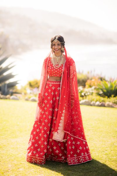 Bridal Lehenga - Bride in a Coral Red Lehenga with Silver Embroidery | WedMeGood #wedmegood #bridallehenga #bridal #lehenga #weddinglehenga #lightlehenga #coral #red #silver