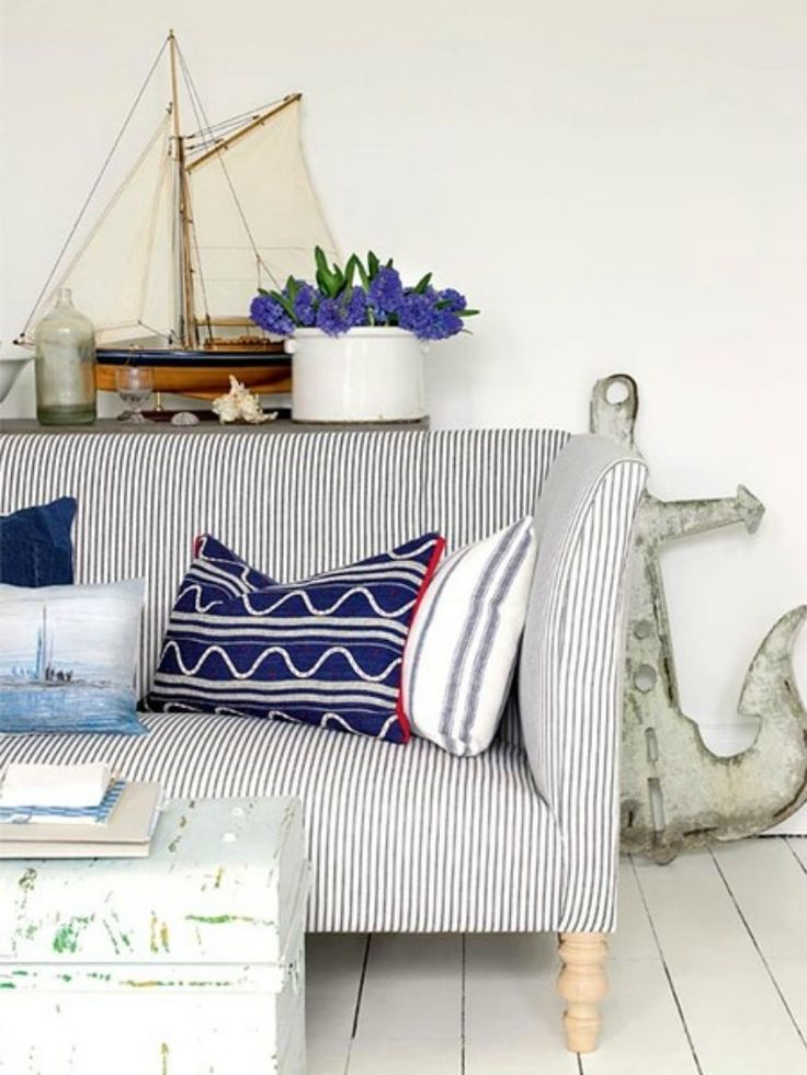 Blue and white ticking coastal stripe sofa is complimented with nautical throw pillows of ships and waves