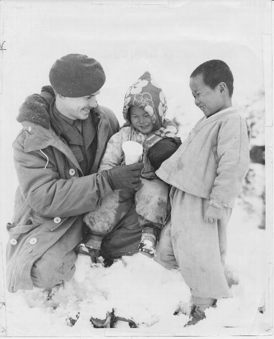 Private Frank Hardy, 2nd Battalion, Princess Patricia's Canadian Light Infantry, showing an imitation ice cream cone to Korean children. Korea. March 4, 1951.