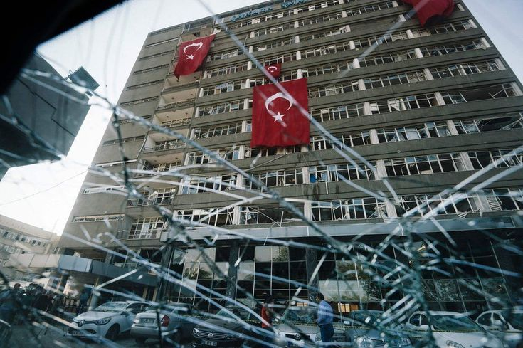 From the shattered window of a car, Turkish flags are seen hanging from the facade of the damaged Ankara police headquarters