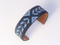 This American Indian beaded bracelet with a Southwestern herringbone pattern is made with the blends of black and blues. The base used for this bracelet is copper wrapped in a soft buckskin. Glass see