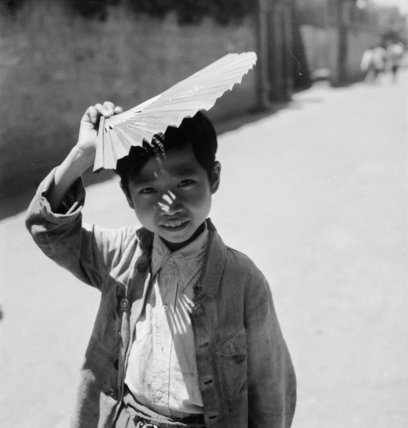 China 1944: A small boy posing with his fan above his head in Chengtu.  Beaton, Cecil  © IWM (IB 2531C)