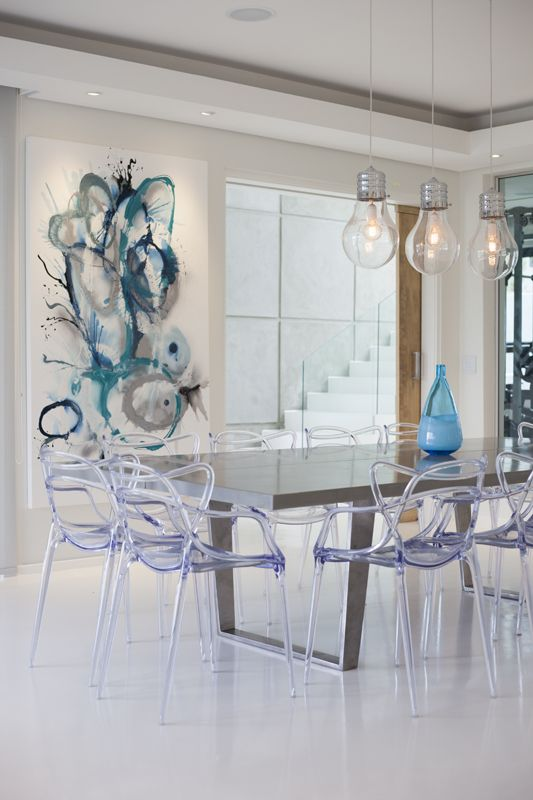 Dining room with beautiful concrete custom table, contemporary art and mix of high gloss white floors and wooden doors