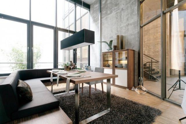 une banquette noire et une table à manger en bois sur le tapis gris