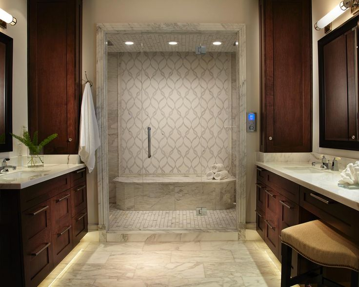 Rich brown his and hers vanities flank a stunning marble shower in this transitional master bathroom.