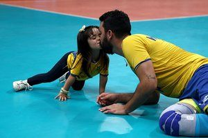 William Arjona of Brazil celebrates victory over Russia with his daughter following the men's volleyball semi-final