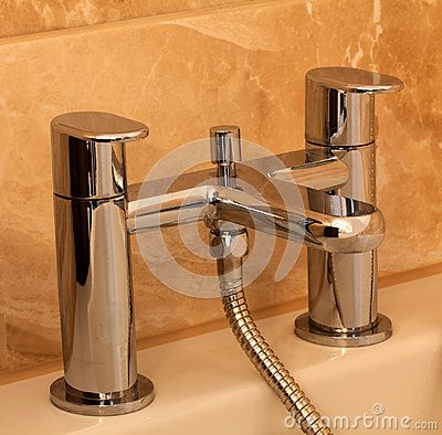 A modern mixer chrome bath taps with marble effect tiles in the background.
