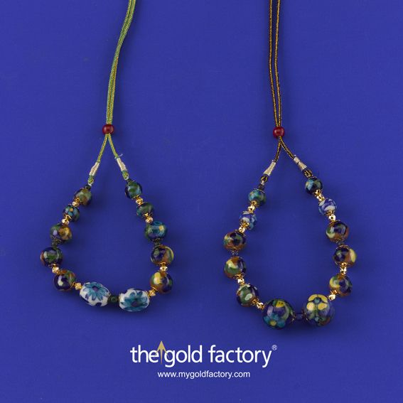 Floral Jaipuri ceramic beads strung with chhela gold spheres and with tassels at the back so that they may be adjusted to size easily become fine jewellery with a bohemian chic with that touch of pure 22K hallmarked gold. Light, innovative, affordable jewels from The Gold Factory. We put the fun back in gold.  From left to right: 1) 3 gm and price Rs. 9900/- 2) 3.200 gm and price Rs. 10,200/-
