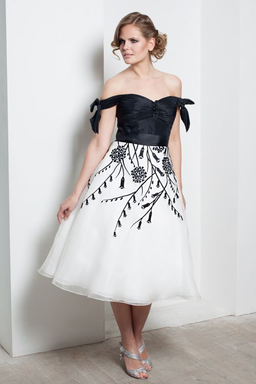 """""""Tiffany""""  : With a taffeta bodice and layered silk organza skirt which falls to just below the knee, this gently delicate dress is ideal for an understated, yet feminine look. With trailing flowers falling from the waist and an a-line skirt, you can be sure that this silhouette will work for you.  The shoulders are exposed with the addition of bows to each side, adding enough detail to catch the eye and yet maintaining this simple and elegant style."""