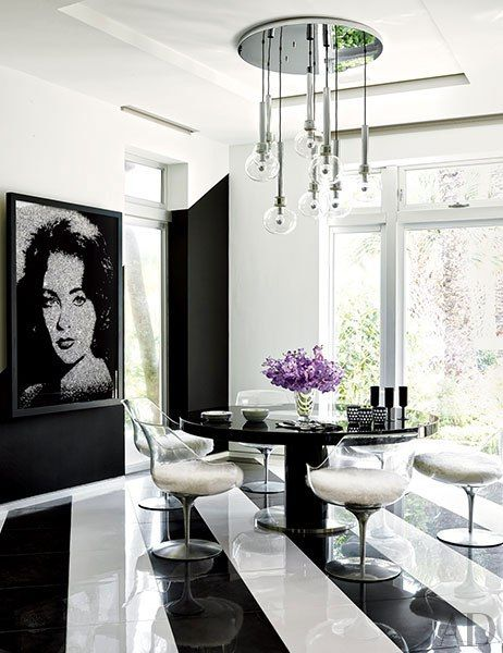 BREAKFAST AREA In the breakfast area, Vik Muniz's ode to Elizabeth Taylor is mounted near a bespoke Willy Rizzo table encircled by vintage Laverne chairs from JF Chen.