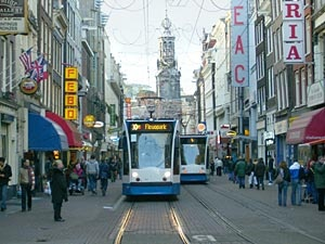 """Amsterdam Trams(11.161)""""The blue-and-white tram arrived, and Augustus handed our cards to the driver, who explained that we needed to wave them at this circular sensor."""" They rode the blue and white trams to the restaurant."""