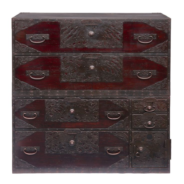 Two-piece dark red lacquered woodenclothing chestfrom the island of Sado (ishodansu) with heavy metal work and strengthened corners. The large key-plates are decorated with a phoenix-bird. The upper part of the chest has two full-wide drawers, the lower part has two large drawers and two smaller drawers and a compartment behind a door. The compartment…