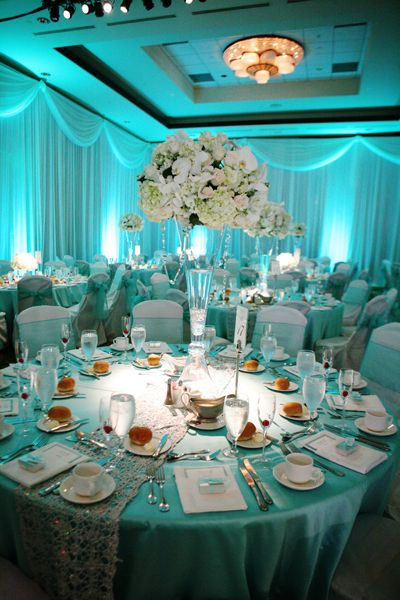 Soft blue lighting with white, blush, and green centerpieces #tiffany blue #wedding #uplighting http://www.discoverydecorlighting.com
