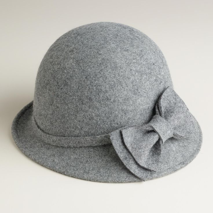 This hat features a 1920s inspired asymmetrical silhouette and grosgrain ribbon for a versatile and stylish look.