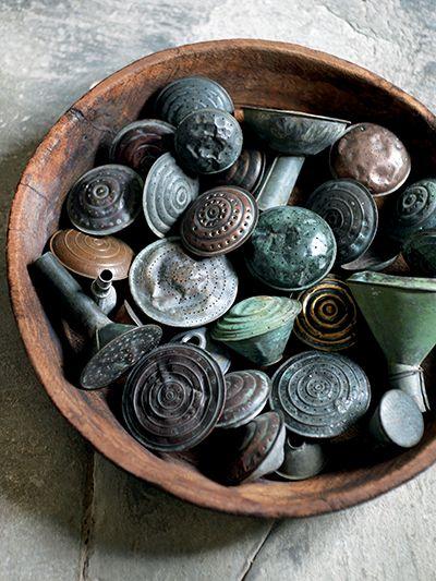 In een sobere, houten schaal komt een verzameling handgemaakte, antieke broeskoppen van koper en brons prachtig uit. Het verweerde kopergroene patina draagt bij aan het stoere karakter. Seasons, september 2012