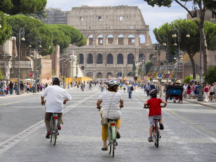 Cycling down Via del Fori Imperiali towards the Colosseum.