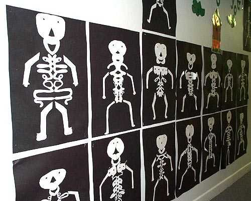"Look closely: students folded white paper in half, wrote their names in cursive, and cut out around their names - this formed the body. They added the head, arms,and legs then mounted their ""name skeletons"" on black construction paper!"