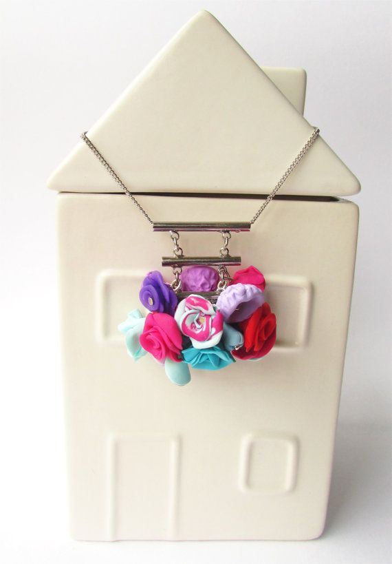 A cluster of fimo flowers hung on a tiered by DelabudCreations
