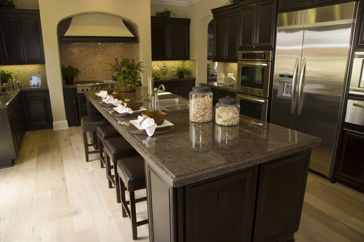 Dark wood cabinet kitchen with dark granite light flooring and tile backsplash
