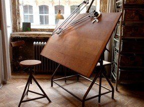 Antique drafting table, hardwood floor in a chevron pattern, and