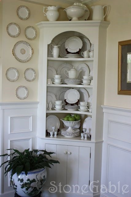 small space corner hutch with curved shelves and high wainscoting - i even like the plates displayed on wall next to it!