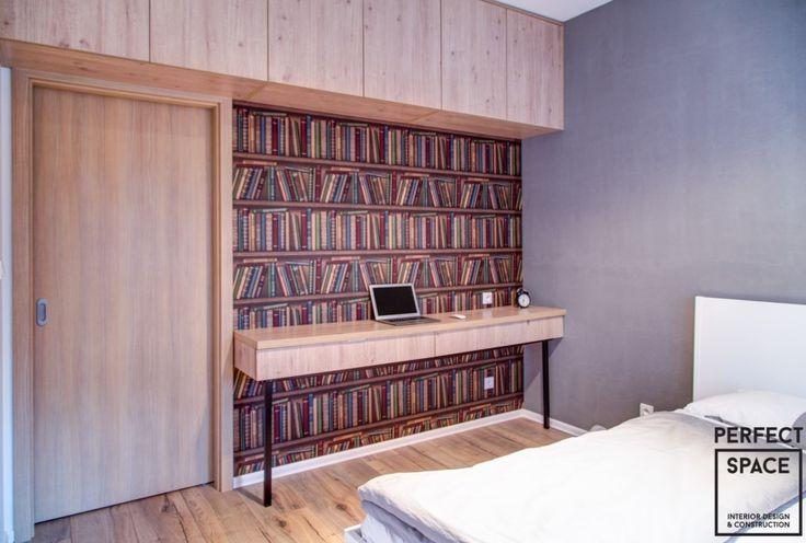 Klasyczna sypialnia z łóżkiem i systemem szafek umieszczonych pod samym sufitem. Wnętrze urozmaica tapeta imitująca regał z książkami.
