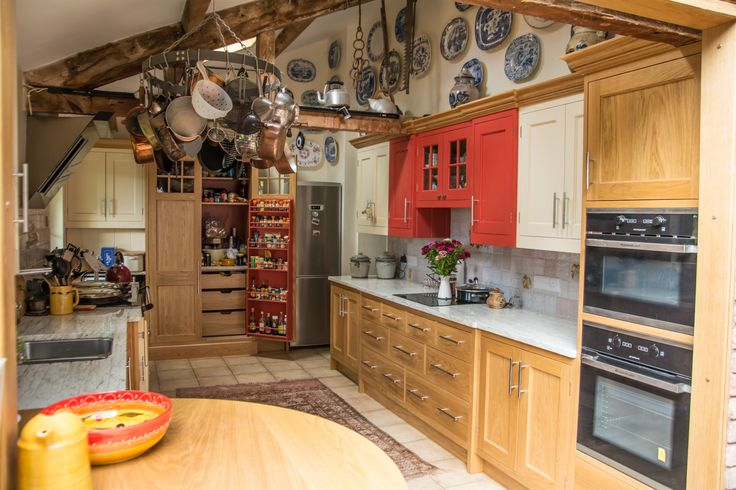 A more colourful country kitchen custom fitted under the exposed beams. Natural wood and hand painted cabinets with full length spice rack fitted into the Pantry Cupboard.