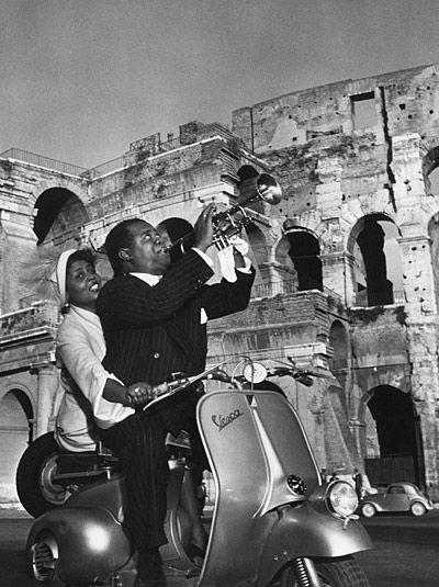 VESPA~Louis Armstrong by the Colosseum in Rome, Italy, on an early model Vespa.