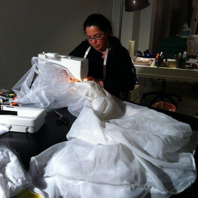 Kika modifying a bridal dress in her sewing atelier.
