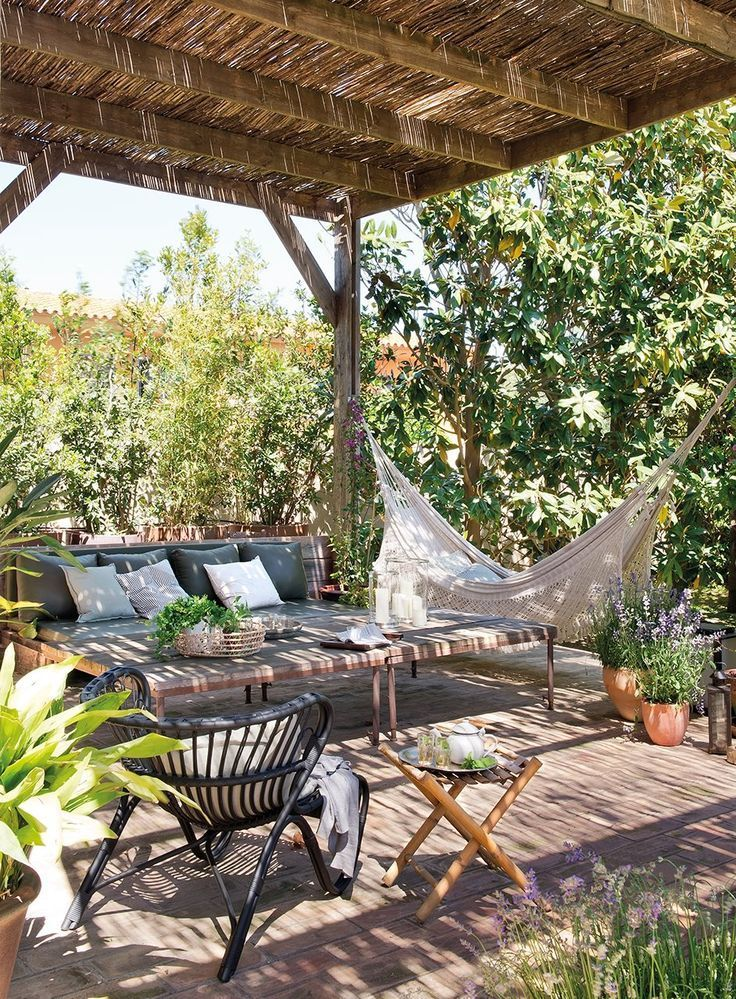 I need this! A sunny but shady back patio with comfy seating, a coffee table, and a hammock, surrounded by lush foliage!