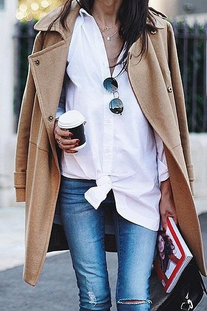 A camel coat, a white button-down, and skinny jeans