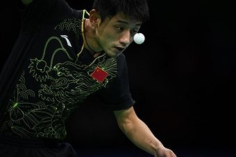 China's Zhang Jike eyes the ball as he serves against China's Ma Long in their men's singles final gold medal table tennis match at the Riocentro venue during the Rio 2016 Olympic Games in Rio de Janeiro on August 11, 2016. / AFP / Jim WATSON