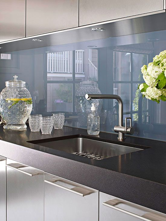 A 3-inch-thick black granite countertop is the perfect stone to contrast the back-painted glass backsplash. The smooth, glossy finish of the granite transitions almost seamlessly to the backsplash,