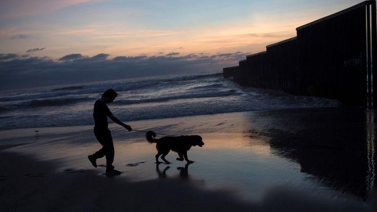 MURO. Un hombre y su perro recortan sus siluetas contra un paisaje al caminar al atardecer en la costa del Océano Pacífico, cerca del muro de la frontera de que separa Tijuana, México con San Diego, California, EE.UU., el martes 4 de abril de 2017....