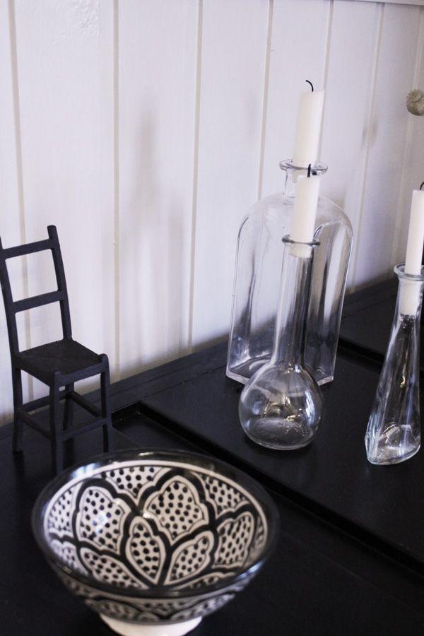 Plåtskåp i svart med text. Vita ljus i glasflaskor. Svart stol i gjutjärn som inredningsdetalj. Svart och vit skål med orientaliskt mönster. Inredningstips i svart och vitt.