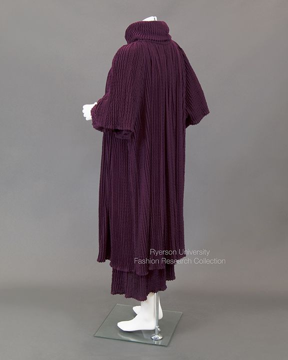 Burgundy texture knit jersey pullover dress with turtleneck collar and long gathered sleeves with matching overcoat with elbow length wide sleeves and self-tie. Label reads: Missioni Creeds Toronto. C. Pre-1990. FRC 2009.01.684 A+B