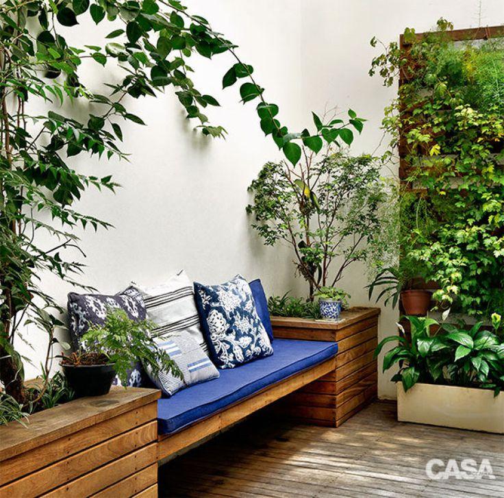 A proprietária cuidou da parede verde, montada com cachepôs pendurados em…