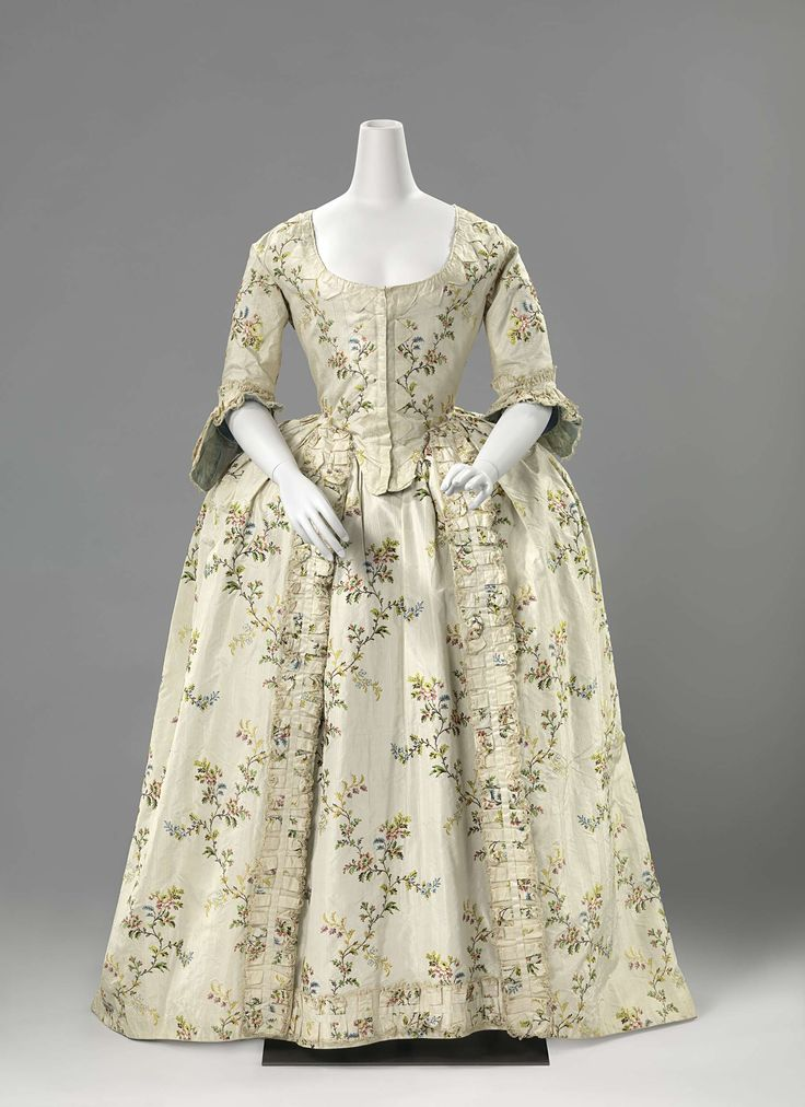 Wedding dress of flowered silk, Anonymous, c. 1760.  In the 18th century brides wore dresses in light shades of blue, yellow, and pink or with fashionable woven or embroidered patterns. Only royal brides wore (silvery) white on their wedding day. This dress consists of a robe and a skirt, both embellished with ruffled flounces of the same material.