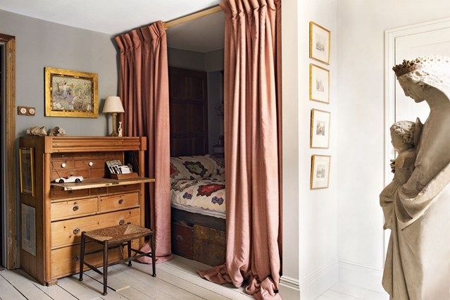 designer Patrick Williams of Berdoulat design, has been turned in to a charming sleeping nook. Enclosed behind the curtain are shelves, and a lamp for reading. The room is painted in Farrow and Ball's 'Lamp Room Gray'; while the random-width floorboards were bought on eBay.