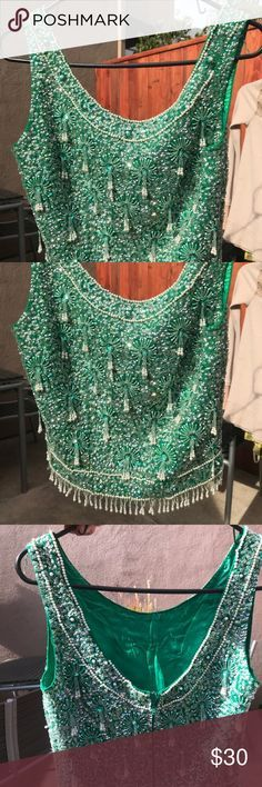 VINTAGE irridescent beaded green top Beautiful for a holiday party. Looks ultra stylish with a full maxi skirt, velvet preferably! Gorgeous, sparkly, pearlescent beading and sequins on classic xmas-tree green! Allover beaded tassels and beaded fringe around waist. Hits high on the waist, around belly button. Deep scooped back and scoop neckline. 100% wool, heavy weight. I am sooo in love with this piece of clothing. Worn confidently, it looks so chic with opera gloves and sparkly jewelry…