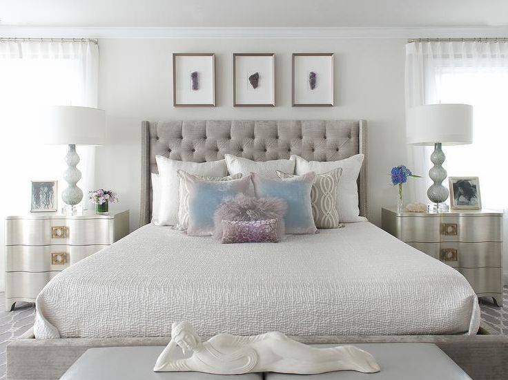 Contemporary gray and silver bedroom boasts a gray velvet tufted wingback bed dressed in white bedding topped…