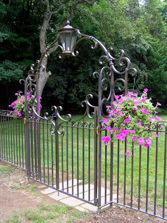 Jozef Custom Ironworks | Iron, Bronze, Curved Stair Railings, Spirals, Gates, Hand forged bronze garden gate and decorative arch with lantern. This piece brings charm to this backyard. Natural patina finish.