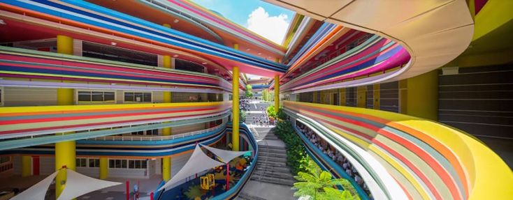 Joyful and Vibrant Primary School in Singapore  The Nanyang Primary School in Singapore decides to create an extension for its pupils : the project of studios 505 and LT&T is born the first objective of which was to create a common space to all in the heart of the school. The fascinating and vibrant color palette is thought for strategically tempt more to study the pupils and to favor a pleasant space where we want to come. The long horizontal colored strips never seem to be endless…