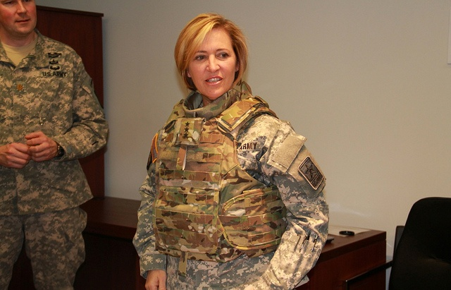 Lt. Gen. Patricia Horoho, Army Surgeon General, tries on the new tactical vest specifically designed for the female physique.  While providing the same high-level ballistic protection, it has an improved quick release system, narrower shoulders, front ballistic plate insertion, more adjustability in the waist area, and a collar that can accommodate the regulation hair styles worn by women in the field. (Photo by Glenda S. Smith)