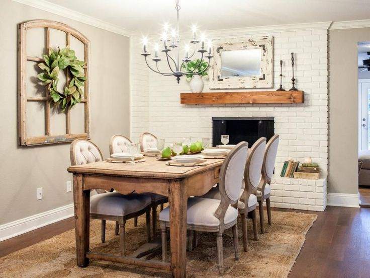 The dining room gets updated with a new redwood mantel, farm table, dark metal chandelier and black accents offering contrast against the white brick.