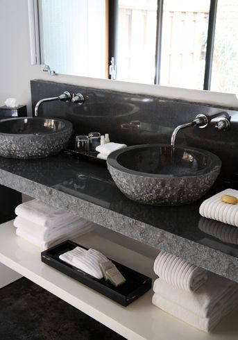 Modern bathroom design with gorgeous black granite vanity. A pair of carved black granite vessel sinks sit on a thick black granite countertop with wall mounted faucets. The edges of the granite are left natural and unpolished.